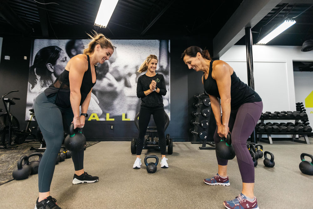 Two young women working out with a personal trainer